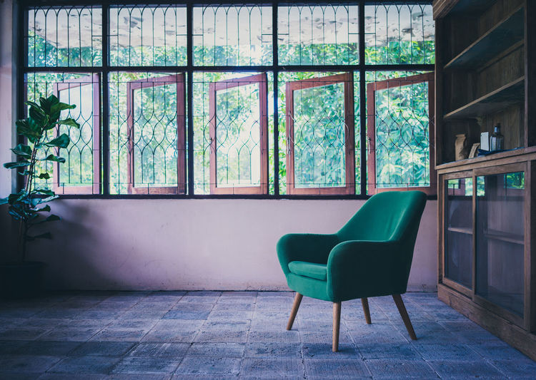 Window Indoors  No People Chair Seat Day Flooring Absence Empty Domestic Room Green Color Table Glass - Material Plant Architecture Tile Wall - Building Feature Tree Tiled Floor Turquoise Colored Old Room  Armchair Grunge Copyspace Retro