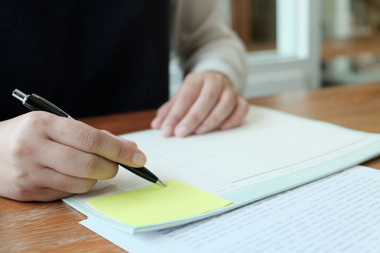 Midsection of businesswoman writing on paper at desk in office