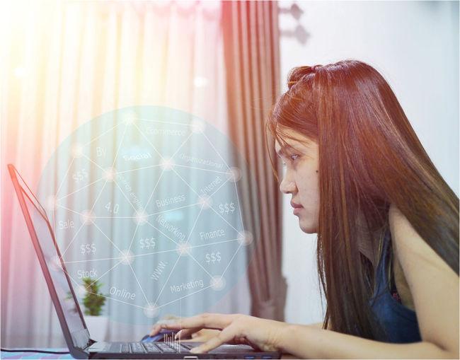 Digital composite image of woman using laptop