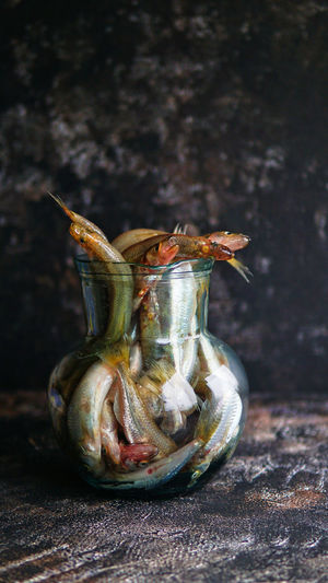Close-up of fishes in jar on table