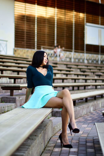 Full length of young woman relaxing on bleacher at amphitheater