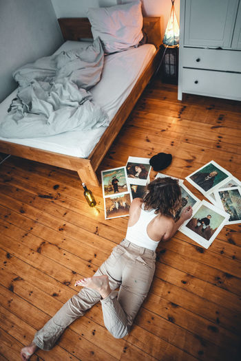 Flooring Indoors  Hardwood Floor High Angle View Wood Home Interior One Person Full Length Real People Lifestyles Leisure Activity Women Rear View Lying Down Bed Furniture Relaxation Men Adult Parquet Floor Hairstyle