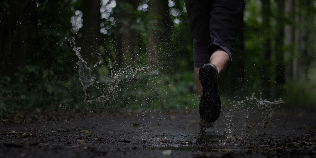 Low section of man running outdoors during rainy season
