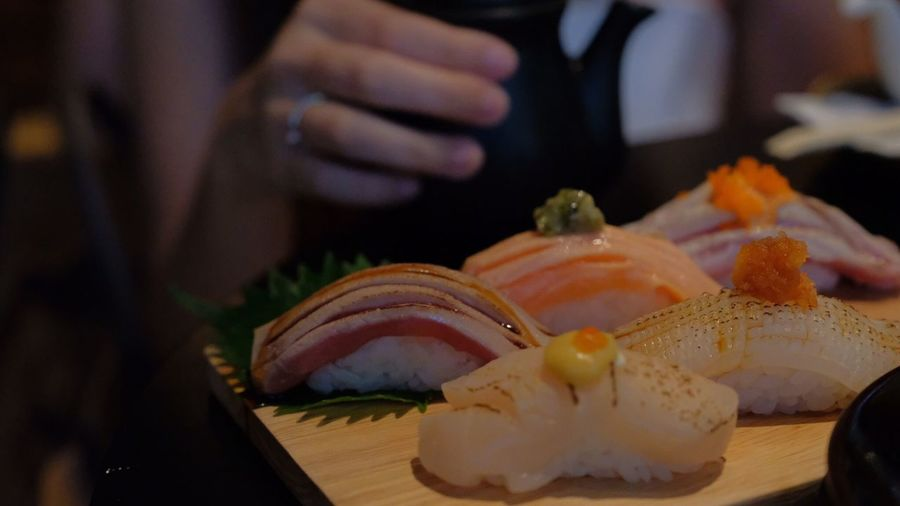 Cropped image of woman reaching towards sushi
