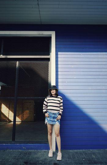 Full length portrait of girl standing against building