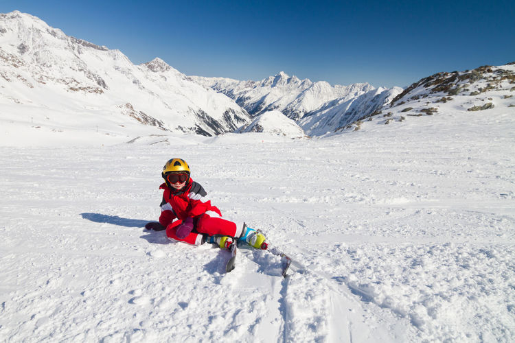 Teenage girl skiing on snow covered land against blue sky