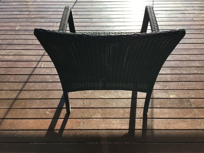 Back Brown Chair Day Deck Decking Facing Facing Away Floorboards Lines No People Outdoors Reflection Shadow Sunshine Wicker Wood