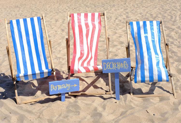Deckchairs on sand at beach