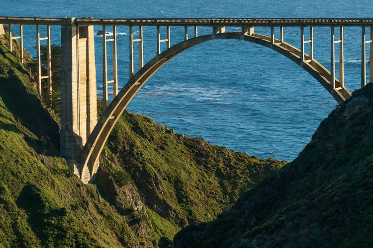 Arch bridge over sea against blue sky