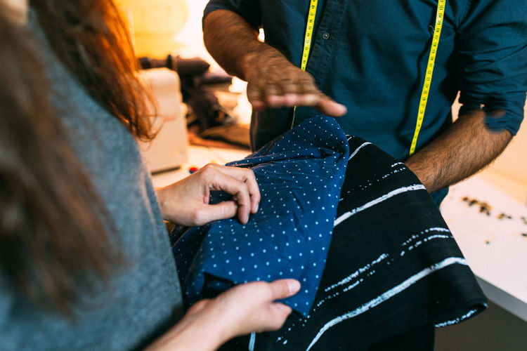 Midsection of coworkers discussing clothing at store