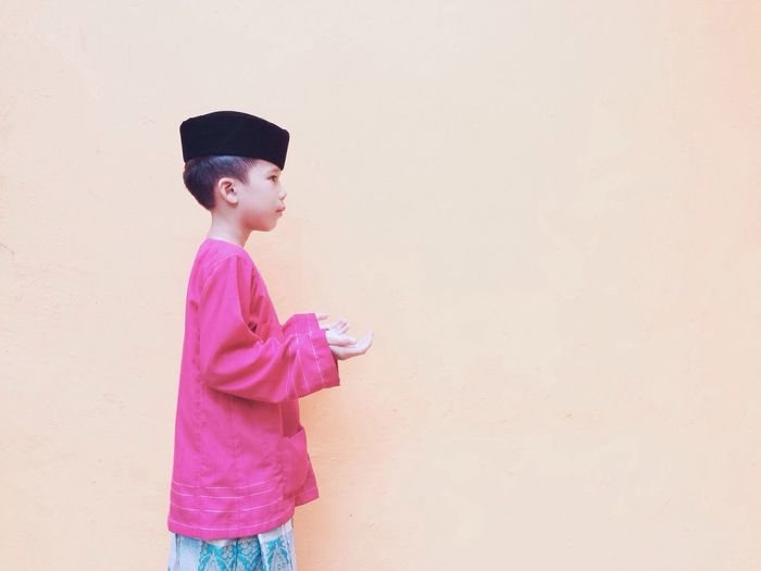 Side View Of Boy Wearing Traditional Clothing Against Wall