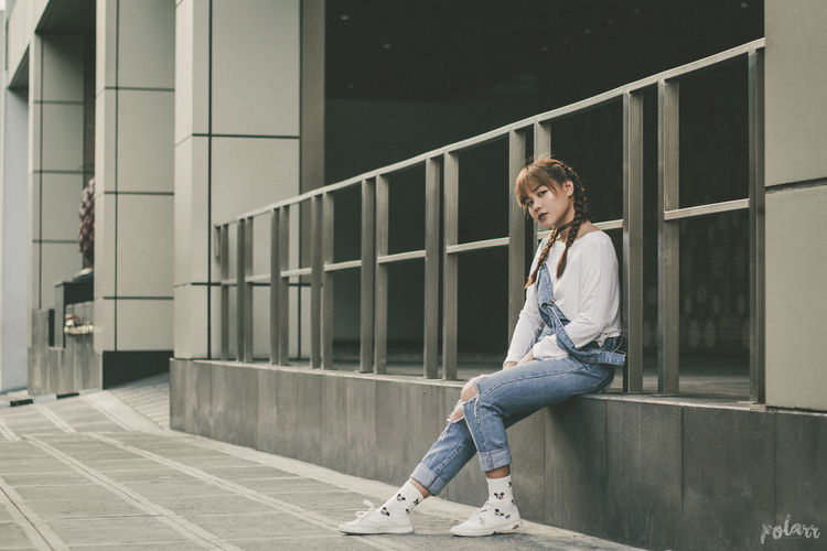 Portrait of woman sitting against railing