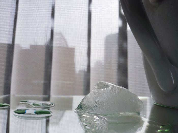 Close-up of glass on table against window at home