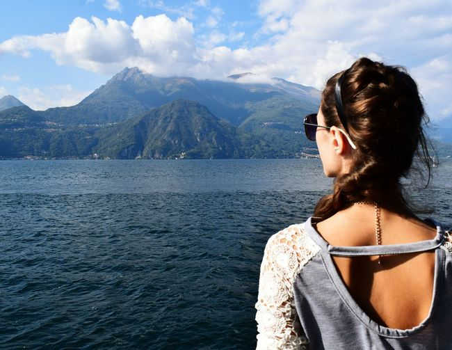 Rear View Of Woman Standing By River Against Mountains