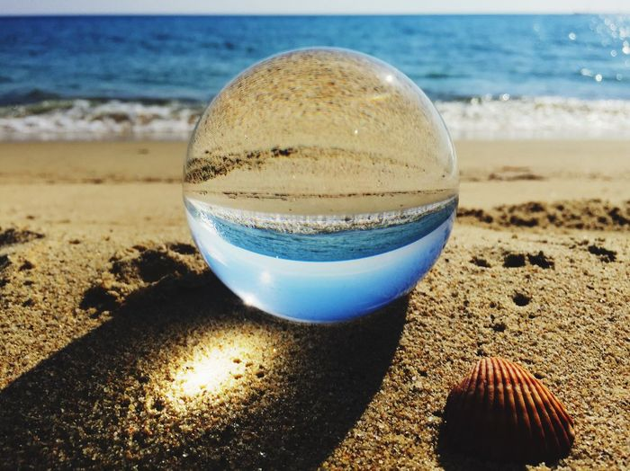 looking for the summer (through a lensball) Sea Shells Lensball Land Beach Sand Sea Water Nature Sunlight Close-up Horizon Over Water Beauty In Nature Focus On Foreground