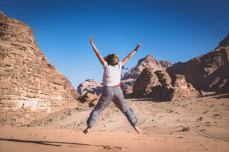 Rear view of woman jumping over field at desert