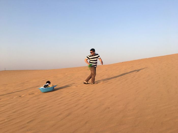 Father pulling son in small bathtub at desert against sky