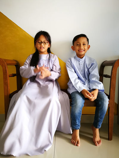 Siblings sitting on bench at home during eid-ul-fitr