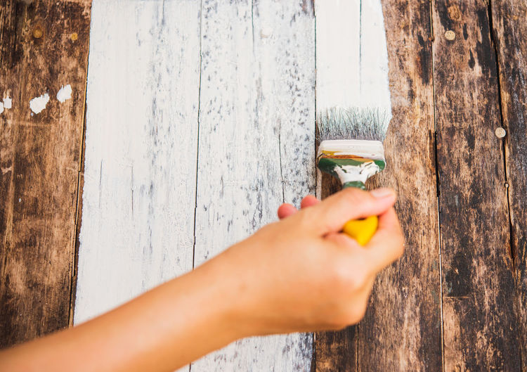 Cropped image of person painting wooden planks