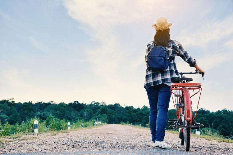Rear View Of Woman With Bicycle On Road Against Sky