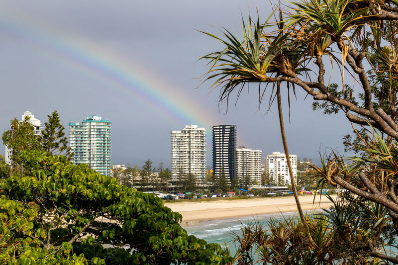 Scenic view of rainbow over city buildings