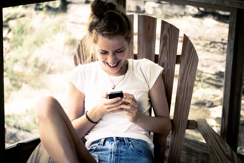 Young woman using mobile phone while sitting on chair
