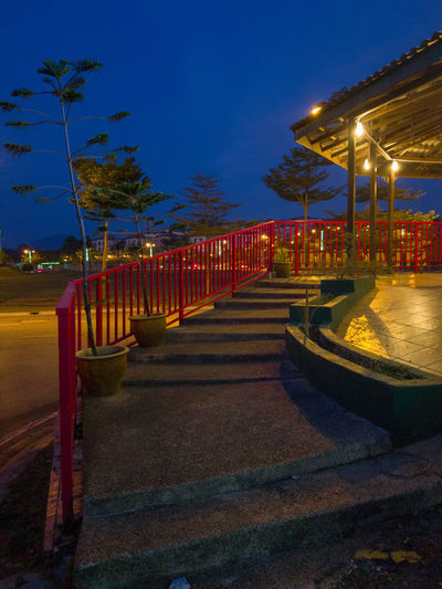 View of illuminated footpath at night