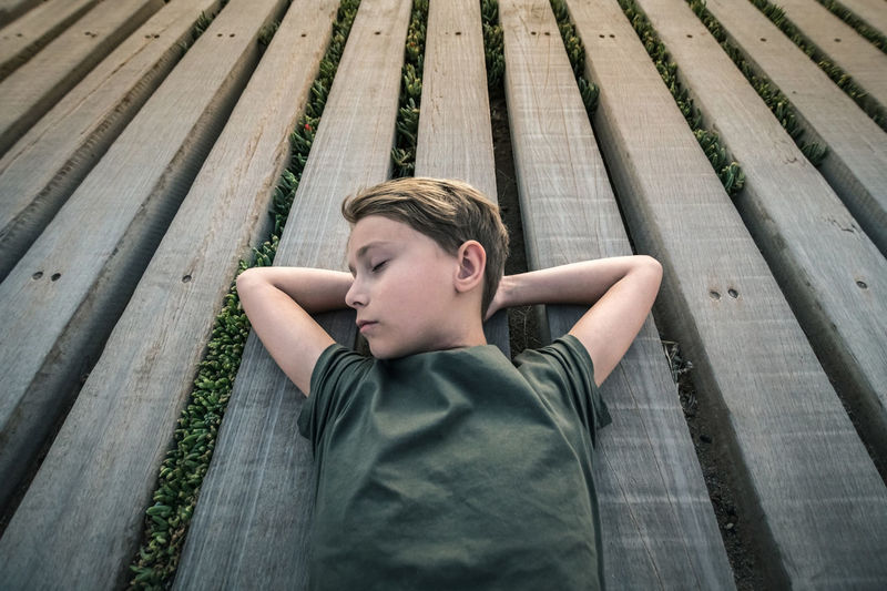 High angle view of boy lying on wooden floor