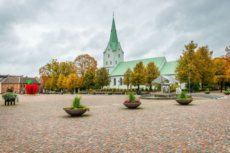 Dobele. Latvia. Autumn landscape with church and ancient market square with fountain. Architecture Autumn Autumn colors Baltic Baltic Countries Church Dobele Latvia Tree Architecture Baltic States Building Building Exterior Built Structure Cloud - Sky Clouds Day Foliage History Nature No People Outdoors Religion Sky Street