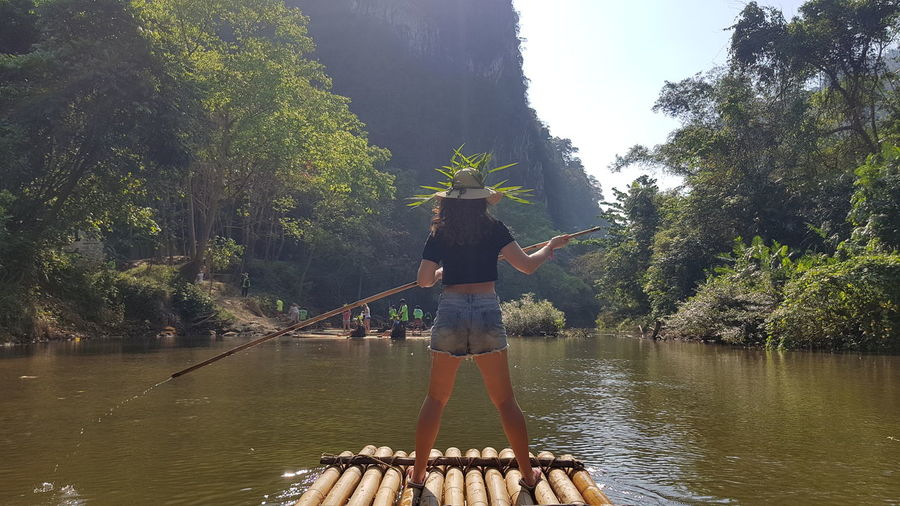 Rear view of woman standing on wooden raft in lake