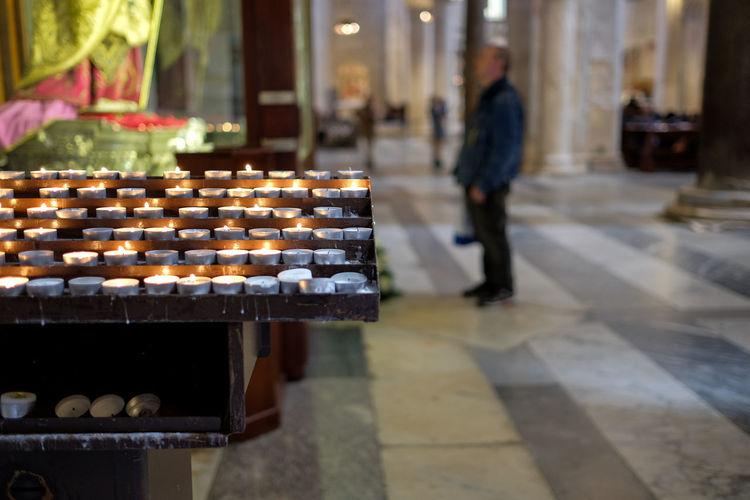 Lit tea light candles against man standing in church
