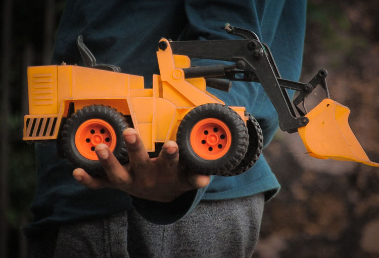 Midsection of man holding bulldozer toy outdoors