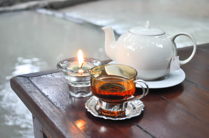 Close-up of candle and herbal tea on table