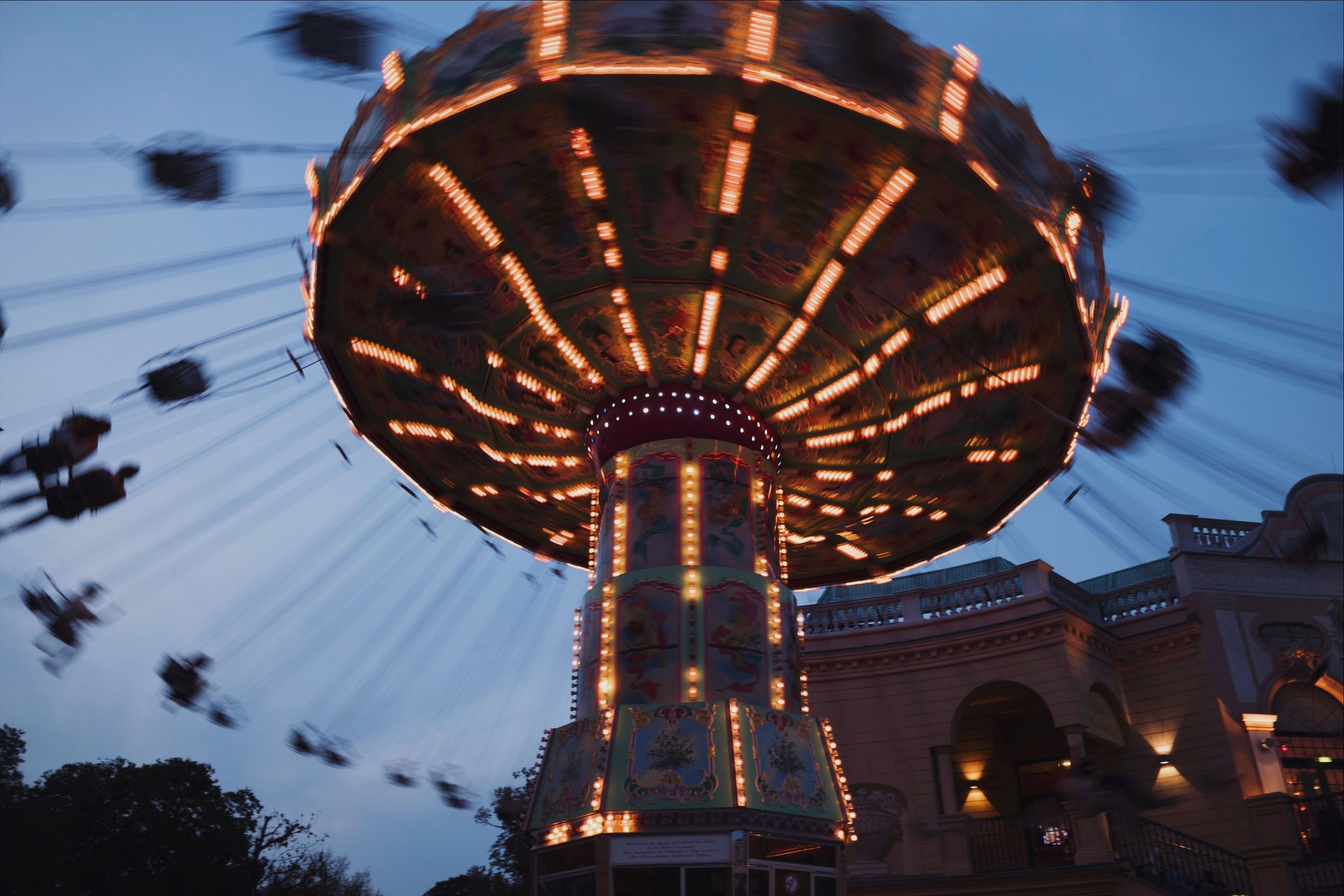 amusement park, amusement park ride, illuminated, sky, arts culture and entertainment, low angle view, chain swing ride, spinning, nature, motion, architecture, dusk, built structure, blurred motion, speed, outdoors, no people, fun, tree