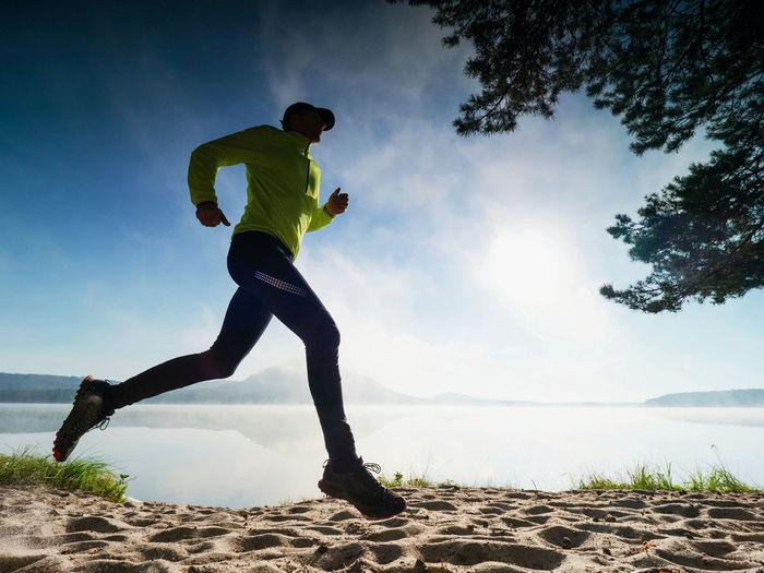 Man running on land against sky