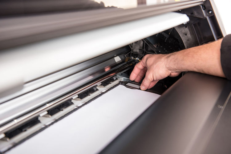 Cropped hand working in printing press