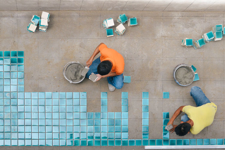Directly above shot of workers installing tiles on floor