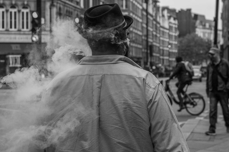 Rear view of man smoking on city street