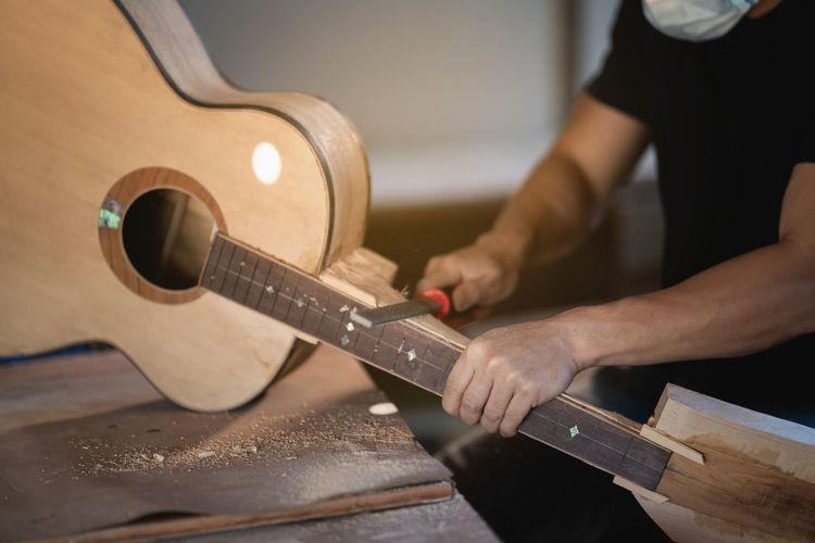 Midsection of man preparing acoustic guitar in workshop