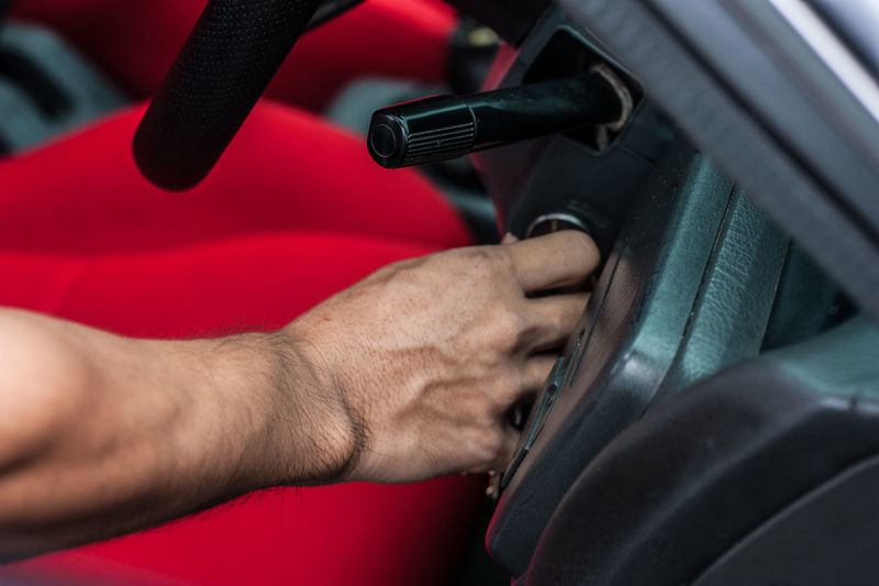 Close-up of hand touching steering wheel in car