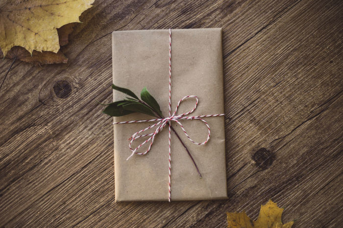 Wrapped gifts on wooden table Christmas Holiday Love Wrap Chritsmas Decoration Gift Paper Wrapped Indoors  No People High Angle View Leaf Close-up Directly Above Wood - Material Table Tied Up Day Brown Fragility
