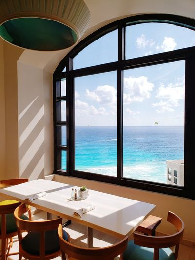 View of restaurant and sea seen through glass window