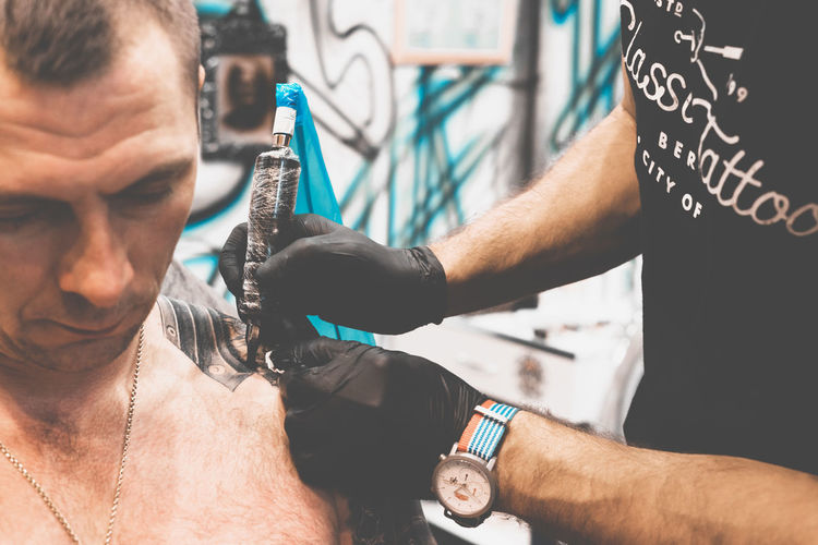 Midsection of man getting tattoo