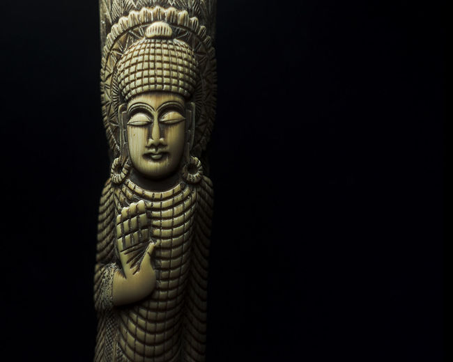 Close-up of statue against black background