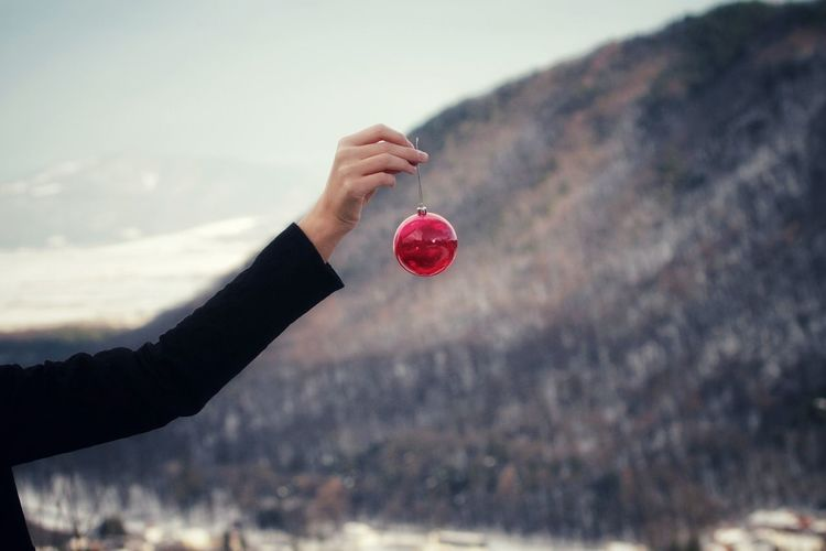 Cropped Hand Of Woman Holding Bauble Against Mountains
