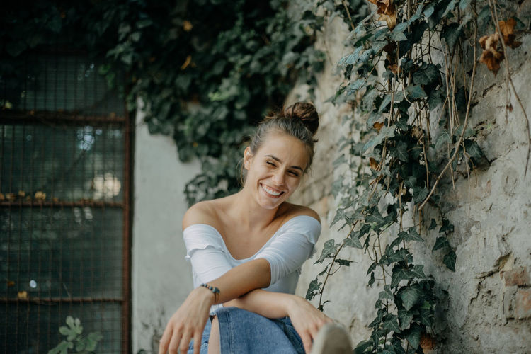 Full length of a smiling young woman sitting against wall