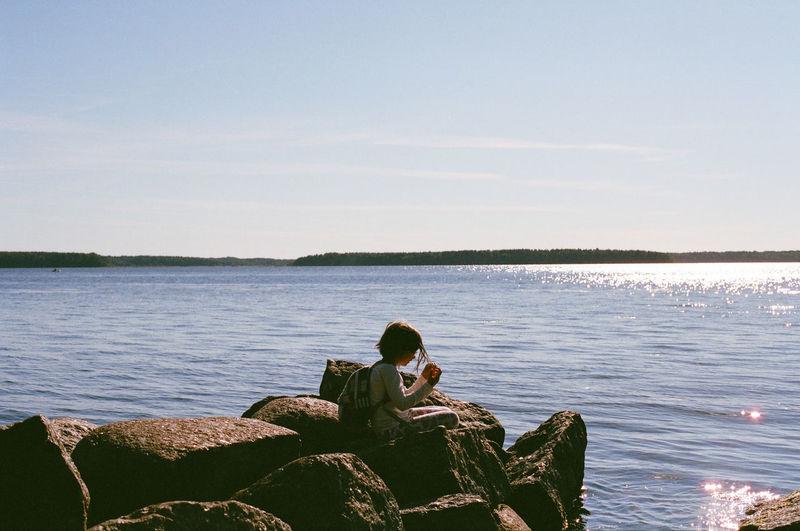 Girl Sitting On Groyne In Sea Against Sky