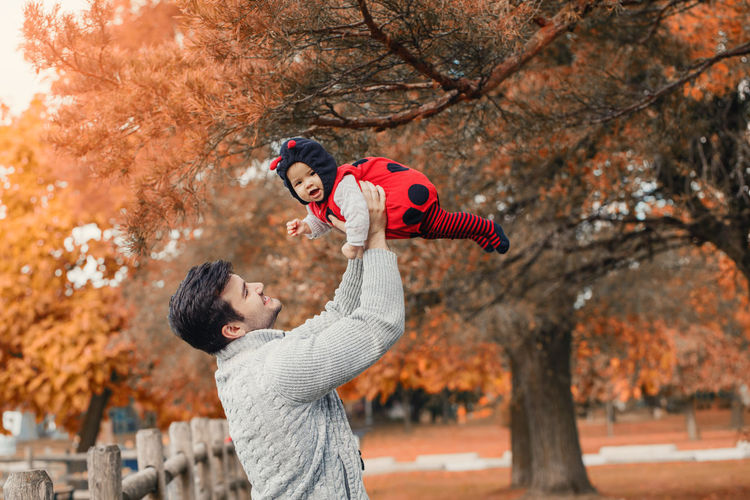 Father picking up daughter while standing against trees during autumn