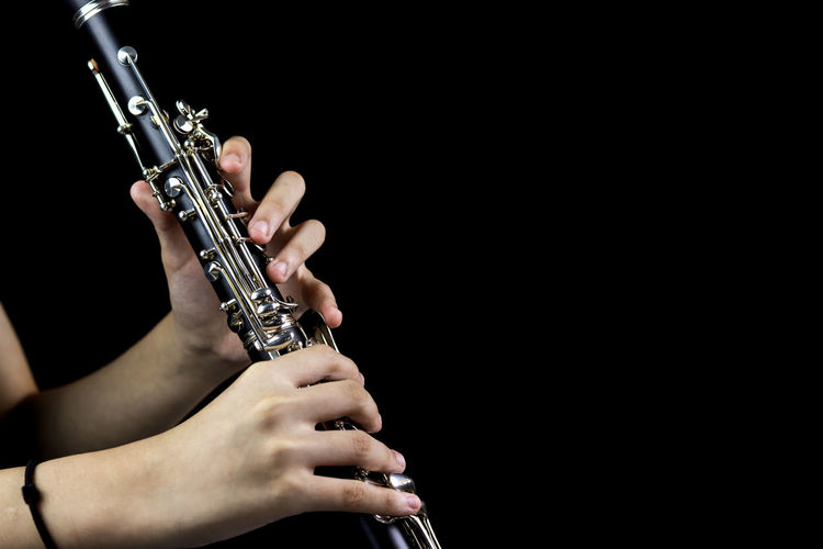 Music Instrument Clarinet Player, Clarinet Player Isolated on black Music Musical Instrument Arts Culture And Entertainment Black Background One Person Studio Shot Human Hand Indoors  Musician Hand Artist Holding Performance Human Body Part Playing Real People Copy Space Unrecognizable Person Midsection Finger