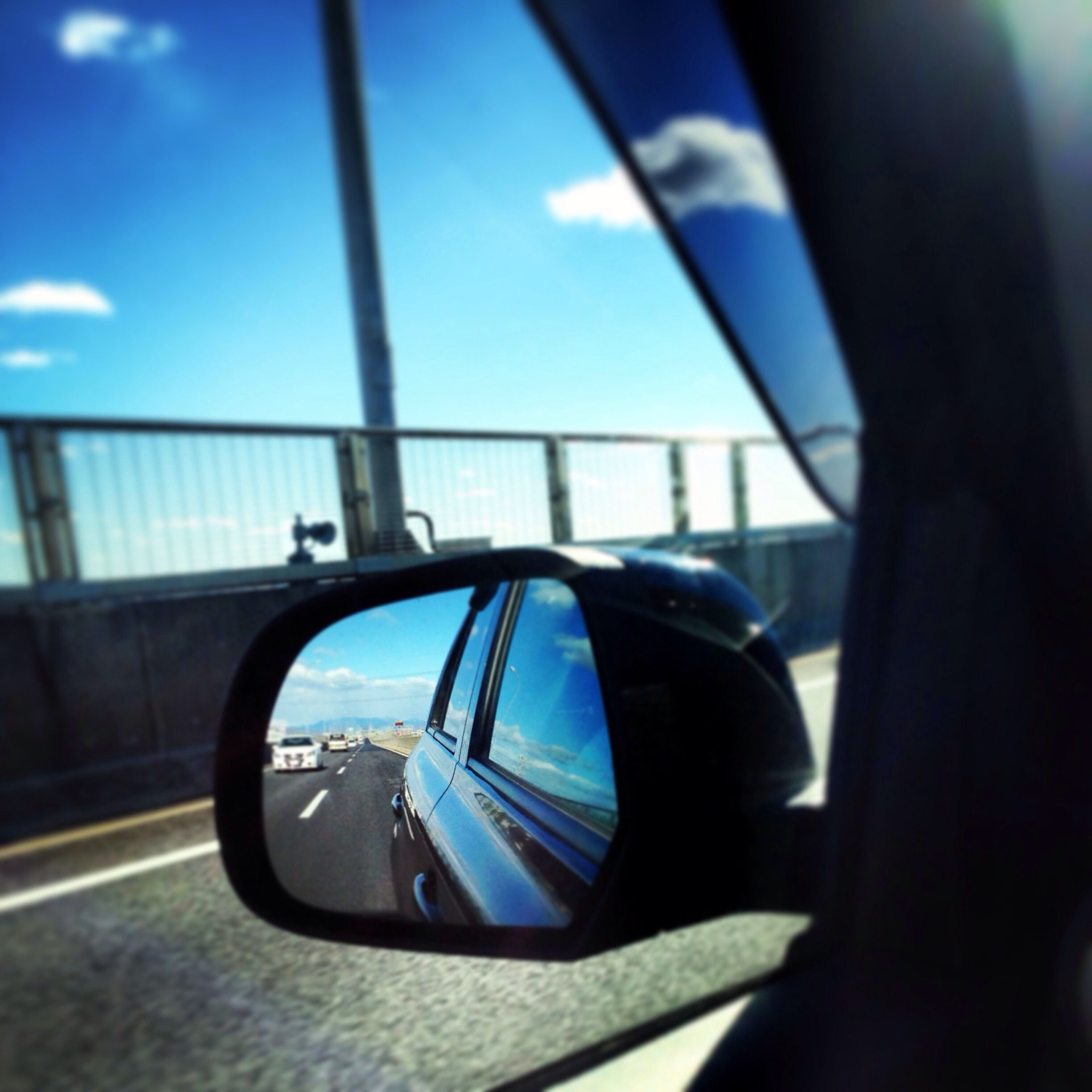 transportation, mode of transport, land vehicle, car, reflection, side-view mirror, road, travel, sky, car interior, on the move, vehicle interior, part of, street, blue, glass - material, cropped, close-up, sunlight, transparent